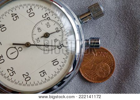 Euro Coin With A Denomination Of Two Euro Cents And Stopwatch On Gray Denim Backdrop - Business Back