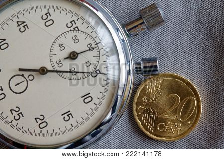Euro Coin With A Denomination Of Twenty Euro Cents And Stopwatch On Gray Denim Backdrop - Business B