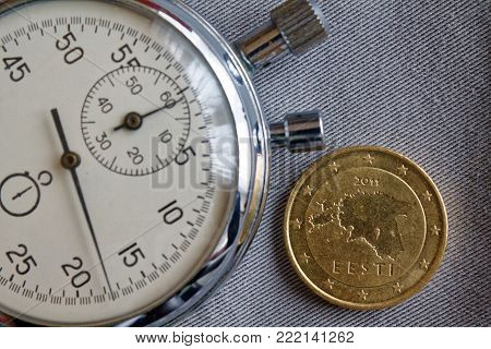 Euro coin with a denomination of fifty euro cents (back side) and stopwatch on gray denim backdrop - business background