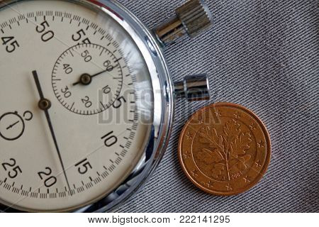 Euro coin with a denomination of 5 euro cents (back side) and stopwatch on gray denim backdrop - business background
