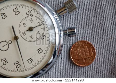 Euro Coin With A Denomination Of One Euro Cent (back Side) And Stopwatch On Gray Denim Backdrop - Bu