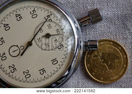 Euro coin with a denomination of 50 euro cents (back side) and stopwatch on white linen canvas backdrop - business background