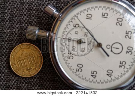 Euro Coin With A Denomination Of 10 Euro Cents (back Side) And Stopwatch On Brown Denim Backdrop - B