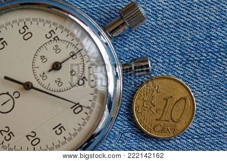 Euro Coin With A Denomination Of Ten Euro Cents And Stopwatch On Blue Denim Backdrop - Business Back