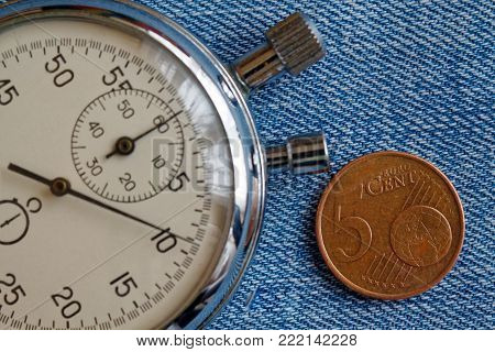 Euro coin with a denomination of five euro cents and stopwatch on blue denim backdrop - business background