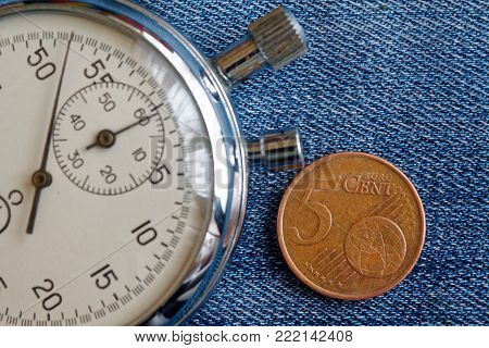 Euro Coin With A Denomination Of Five Euro Cents And Stopwatch On Worn Blue Jeans Backdrop - Busines