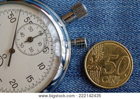 Euro Coin With A Denomination Of Fifity Euro Cents And Stopwatch On Worn Blue Jeans Backdrop - Busin