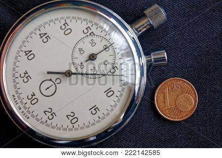 Euro Coin With A Denomination Of 1 Euro Cents And Stopwatch On Black Jeans Backdrop - Business Backg