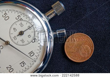 Euro Coin With A Denomination Of Two Euro Cents And Stopwatch On Black Jeans Backdrop - Business Bac
