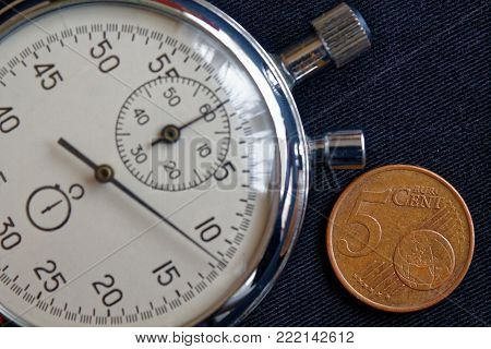 Euro Coin With A Denomination Of Five Euro Cents And Stopwatch On Black Jeans Backdrop - Business Ba