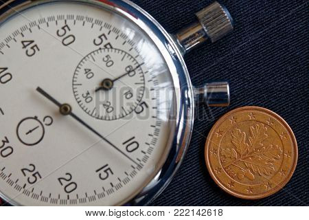 Euro Coin With A Denomination Of 5 Euro Cents (back Side) And Stopwatch On Worn Black Jeans Backdrop