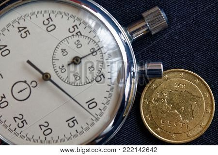 Euro Coin With A Denomination Of 50 Euro Cents (back Side) And Stopwatch On Worn Black Jeans Backdro