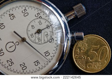Euro coin with a denomination of fifty euro cents and stopwatch on black jeans backdrop - business background