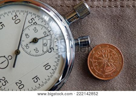 Euro Coin With A Denomination Of 2 Euro Cents (back Side) And Stopwatch On Beige Denim Backdrop - Bu