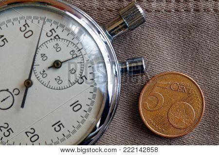 Euro Coin With A Denomination Of Five Euro Cents And Stopwatch On Worn Beige Denim Backdrop - Busine