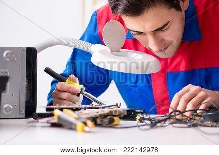 Professional repairman repairing computer in workshop