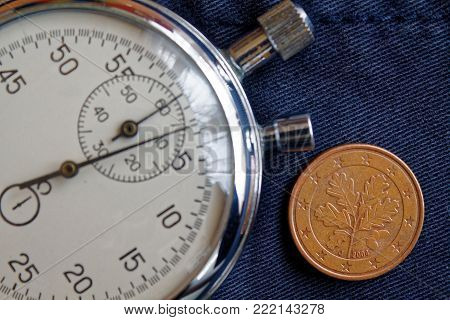 Euro Coin With A Denomination Of 5 Euro Cents (back Side) And Stopwatch On Old Blue Denim Backdrop -