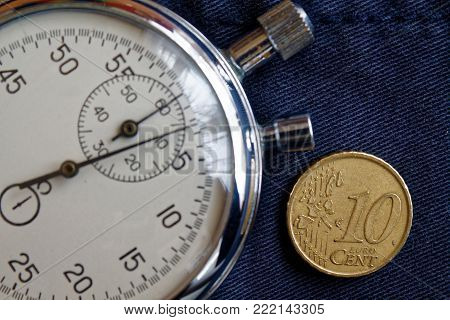 Euro Coin With A Denomination Of Ten Euro Cents And Stopwatch On Old Blue Jeans Backdrop - Business