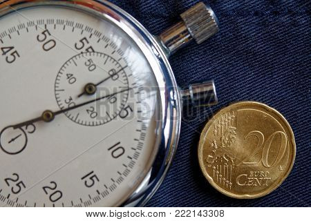 Euro coin with a denomination of twenty euro cents and stopwatch on old blue jeans backdrop - business background