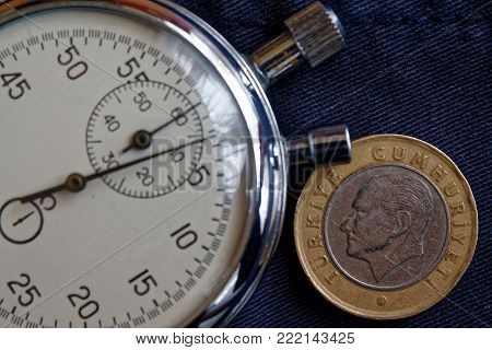 Turkish Coin With A Denomination Of 1 Lira (back Side) And Stopwatch On Dark Worn Blue Denim Backdro