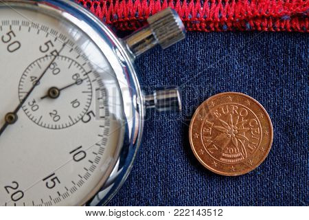 Euro Coin With A Denomination Of 2 Euro Cents (back Side) And Stopwatch On Worn Blue Jeans With Red