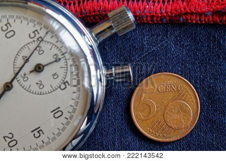 Euro Coin With A Denomination Of Five Euro Cents And Stopwatch On Worn Blue Denim With Red Stripe Ba