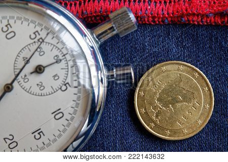 Euro Coin With A Denomination Of 50 Euro Cents (back Side) And Stopwatch On Worn Blue Jeans With Red