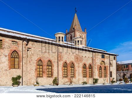 Snowy street and old church under blue sky in Cuneo, Piedmont, Northern Italy.