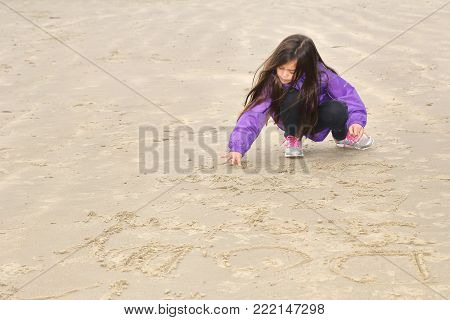 Little girl on a purple coat writing in the sand on a cold deserted beach with space for text