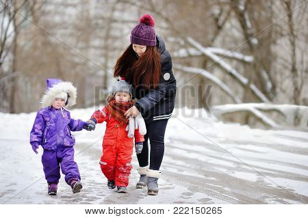 Young asian woman helping caucasian toddler boy anf girl with their winter clothes. Babysitting/childcarer concept.