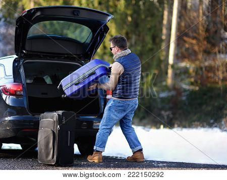 Handsome man going to vacations, loading his suitcase in car trunk. Winter automobile trip in the countryside. Vacation in mountains. Alps, Bavaria, Germany (Deutschland)