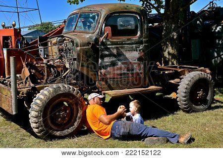 DALTON, MINNESOTA, Sept 8, 2017:  A mechanic father and son  fixing an old truck take a lunch break at the annual Dalton Threshing Bee farm show in Dalton held each 2nd full weekend in September where 1000's attend.