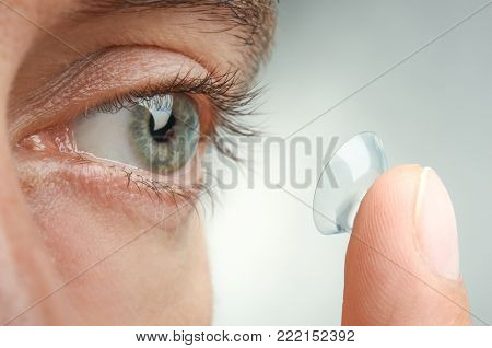 Young man putting contact lens in his eye, closeup