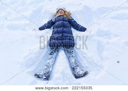 Beautiful little girl wearing navy down jacket and knitted hat playing in a snowy winter park. Kid play with snow and jump in snowy forest. Family winter vacation with child