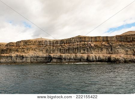Gran Canaria, Canary Islands in Spain - December 16, 2017: Volcanic rock layers. Strata. The beautiful mountains at the coast between Puerto de Mogan and Puerto Rico. Cloudy sky with soft light