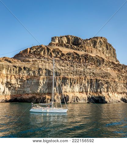 Gran Canaria, Canary Islands in Spain: Sailboat resting in the ocean in front of mountains at the coast at Puerto de Mogan. Volcanic rock layers, strata. Caves. blue sky