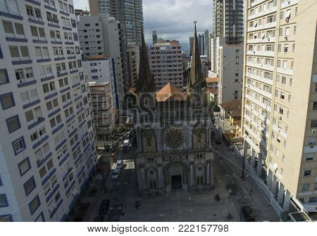 Ancient catholic church surrounded by big building in big city