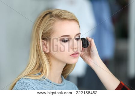 Professional artist creating makeup for beautiful model on blurred background