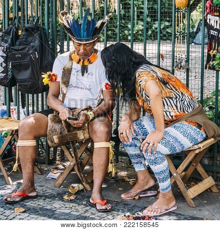 Belo Horizonte, Brazil - Dec 24, 2017: Brazilian indigenous Tupi or Tapuia man dressed in a traditional costume looks at cell phone