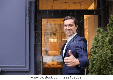 Young man standing near store. Small business owner portrait
