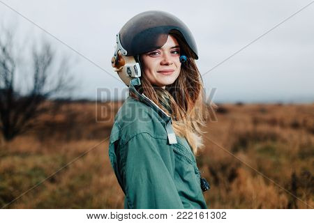 beautiful woman pilot of plane standing in the sunset field in uniform with helmet