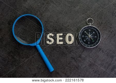 Magnifier, wood alphabet SEO and compass on chalkboard background using as SEO Search engine optimization concept.