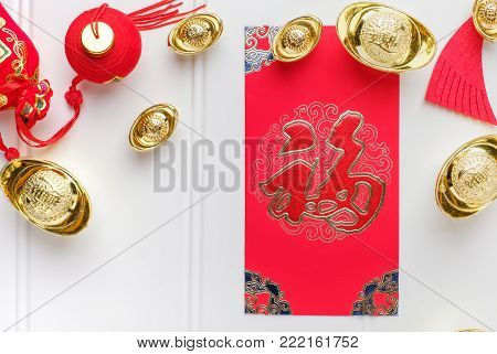 Top view Chinese New year red envelope packet (ang pow) with gold ingots on white wood table top,Chinese Language on envelop mean Happiness and on ingot mean