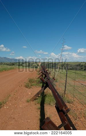 A view down a long stretch of dirt road with an anti-vehicle barrier and fence along the Arizona and Mexico border.