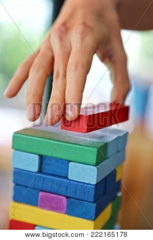 Close-up of asian woman's hand playing colorful wood blocks stack game in morning light , playing and learning background concept