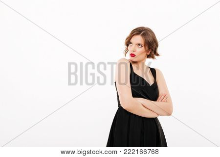 Portrait of an upset girl dressed in black dress standing with arms folded and looking away at copy space isolated over white background