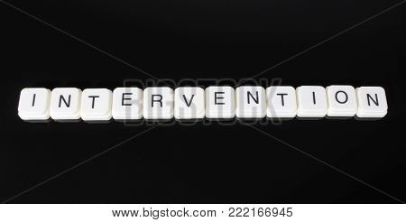Intervention text word title caption label cover backdrop background. Alphabet letter toy blocks on black reflective background. White alphabetical letters. White educational toy block with words on mirror board table.