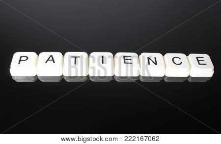 Patience text word title caption label cover backdrop background. Alphabet letter toy blocks on black reflective background. White alphabetical letters. White educational toy block with words on mirror board table.