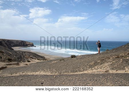 a young caucasian man, seen from behind, carrying a backpack taking a picture with his smartphone of the Viejo Rey Beach in Fuerteventura, Canary Islands, Spain