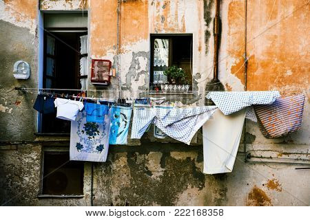 clothes hanging in some clothes lines outdoors in an old building, in the old town of Cagliari, in Sardinia, Italy
